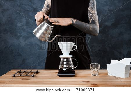 Young handsome male barista brewing coffee. Alternative method pour over. Copy space.