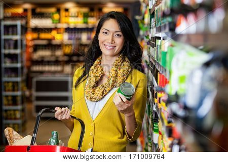 Portrait of smiling woman shopping for groceries in supermarket
