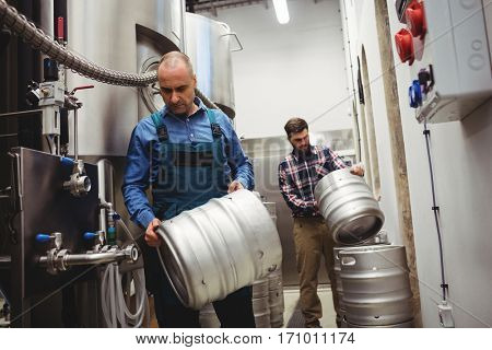 Owner and worker carrying kegs in brweery