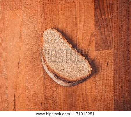 Rye bread on a wooden table. Top view. Fresh fragrant crispy sliced bread. Loaf of bread slices on cutting board closeup. Home-made bread on a wooden background.