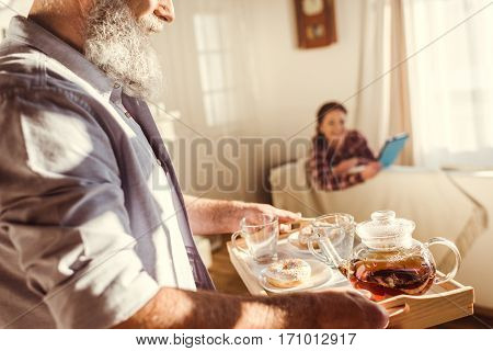 Mature bearded man bringing tray with tea and sweets to woman