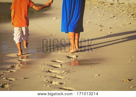 mother and little son walking on beach leaving footprint in sand
