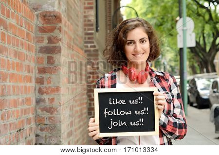 Young beautiful woman holding chalkboard with text