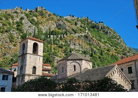 church of St. Mary Collegiate in Kotor Old Town, on background the St. John fortification - Montenegro