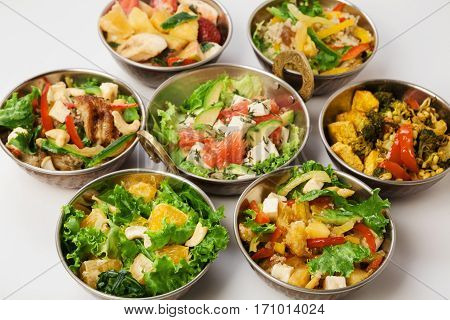 Vegan or vegetarian restaurant dishes, hot spicy indian curry and salads in copper bowls. Traditional indian cuisine meal assortment isolated on white background. Healthy eastern local food