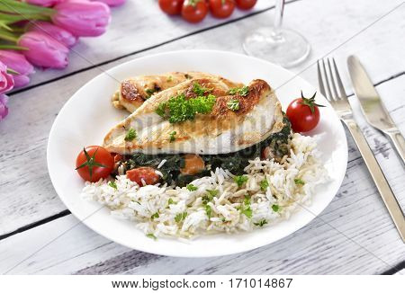 Grilled chicken breast with vegetables, rice and cherry tomatoes. Healthy eating scene, grilled chicken on a white, wooden table.