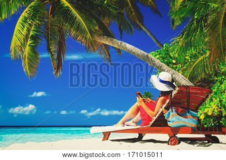 remote work concept -woman with touch pad on tropical beach
