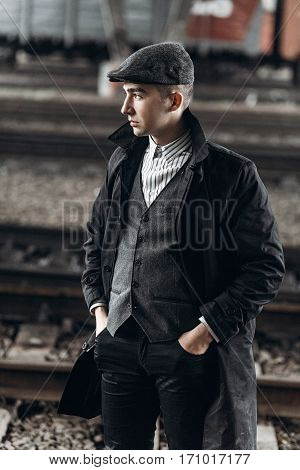 Stylish Gangster Man Posing On Background Of Railway. England In 1920S Theme. Fashionable Brutal Con