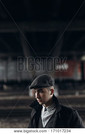 Brutal Gangster Posing On Background Of Railway. England In 1920S Theme. Fashionable Confident Man.