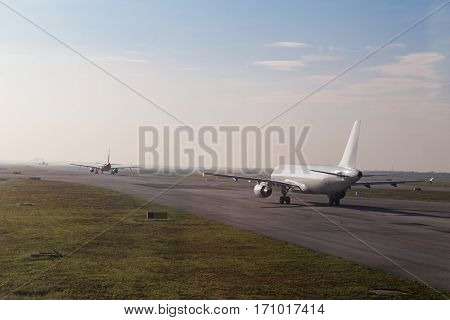 Commercial Airplane Queue Taxiing To Take Off On Runway