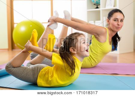 Mother and kid daughter in the gym centre doing stretching fitness exercise. Yoga