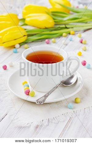 Cup of tea with bonbon on a decoration table with a spring flowers.