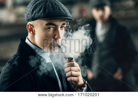 Stylish Men Smoking In Retro Clothes Posing On Background Of Railway. England In 1920S Theme. Fashio