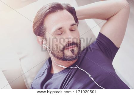 Have a nap. Pleasant adult bearded man resting on the couch and listening to music while sleeping at home