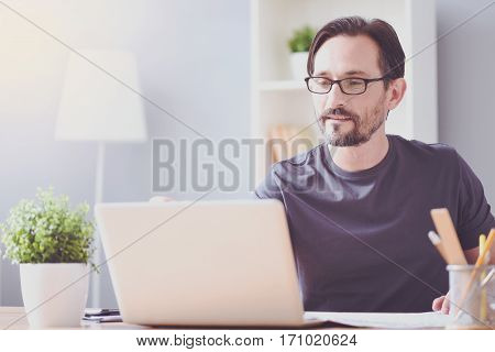 Find inspiration in work. Pleasant delighted bearded man using laptop and sitting at the table while being involved in distance work