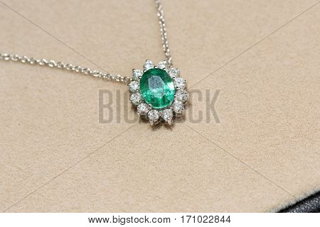 White gold necklace with a pendant with emerald and diamonds