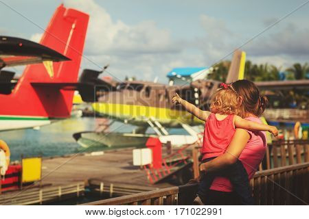 mother and little daughter waiting for seaplane, family travel concept