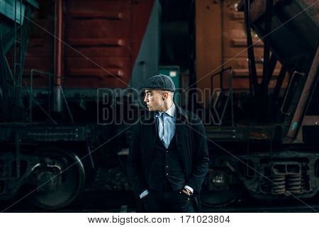 Stylish Gangster In Tweed Outfit Posing On Background Of Railway Carriage. England In 1920S Theme. F
