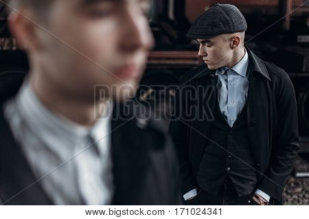 Stylish Gangsters Men, Posing On Background Of Railway. England In 1920S Theme. Fashionable Brutal C