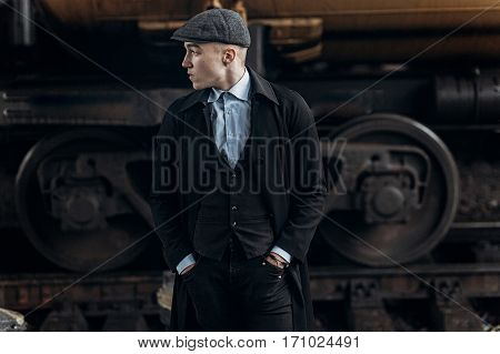 Stylish Man In Retro Outfit, Posing On Background Of Railway. England In 1920S Theme. Fashionable Lo