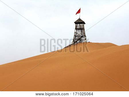 watchtower with red flag in the desert in Shapotou Ningxia province China