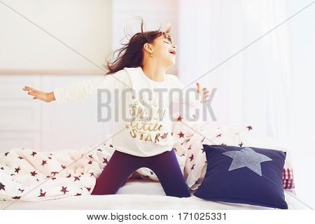 Happy Vigorous Young Girl Wakes Up In The Morning Sun Light, Singing In Bedroom