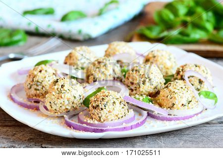 Cream cheese balls on a plate. Cream cheese balls with spices and roasted sesame seeds served with raw onion rings and basil. Quick cheese appetizer recipe. Closeup