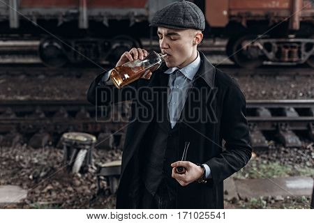 Stylish Gangster Man Drinking. Posing On Background Of Railway. England In 1920S Theme. Fashionable