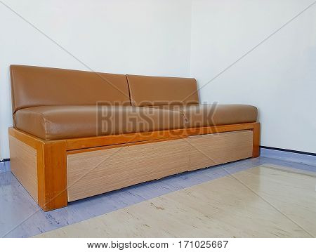 Wooden sofa with leather seats in small room,old sofa,Vintage sofa on white wall background.