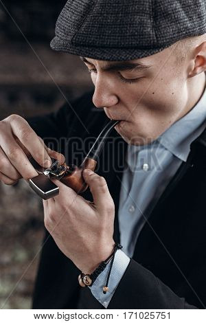 Sherlock Holmes Look, Man In Retro Outfit, Smoking, Lighting Wooden Pipe. England In 1920S Theme. Fa