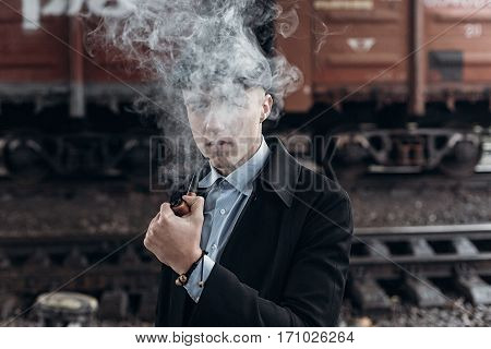 Stylish Gangster Man Smoking. Posing On Background Of Railway. England In 1920S Theme. Fashionable B
