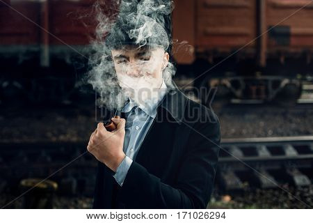 Stylish Gangster Smoking In Tweed Look, Posing On Background Of Railway. England In 1920S Theme. Fas