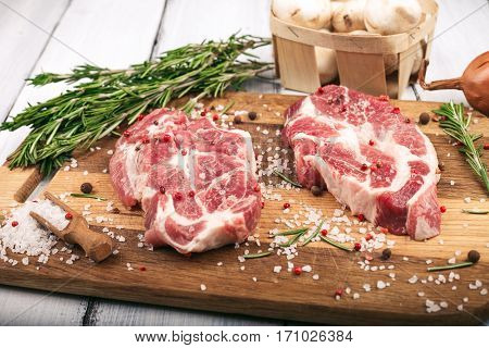 Porky steak with salt pepper and rosemary on wood background.