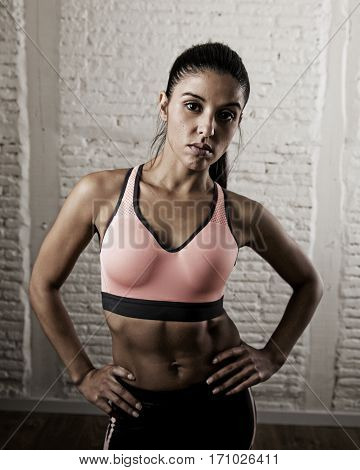 young attractive latin sport woman posing in fierce and badass face expression with fit slim body isolated on gym studio background in healthy lifestyle and fitness concept