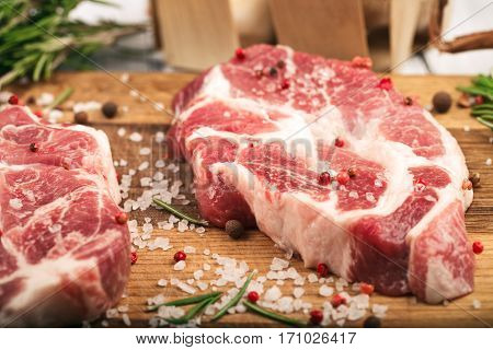 Porky steak with salt pepper and rosemary on wood background. Close up