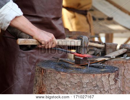 Man's hand with hummer - metal forging process