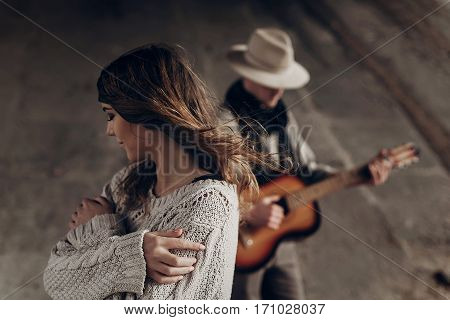 Beautiful Sensual Indie Girl In Hipster Boho Clothes Posing In Front Of Handsome Cowboy Guitar Playe