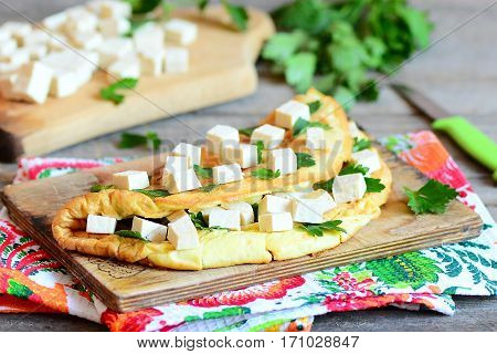 Homemade omelette stuffed with tofu cubes and fresh parsley on a wooden board. Delicious nutritious breakfast for whole family. Rustic style. Closeup
