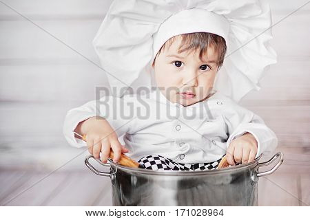 cute little baby. Funny chef sitting in big pan