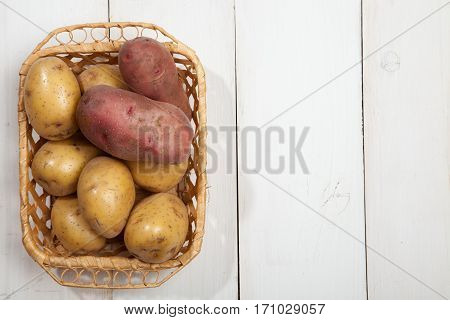 Raw potatoes with burlap on white wooden background top view