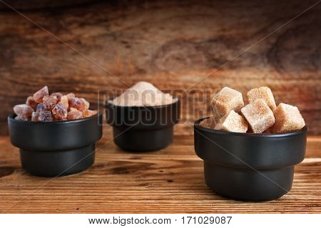 Dice sugar caramelized sugar and brown sugar in small bowls on a wooden background