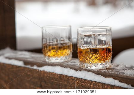 Two whiskey glasses in the snow on a winter background.