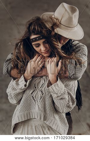 Strong Cowboy Man In White Stylish Hat Hugging Beautiful Brunette Hipster Girl From Behind