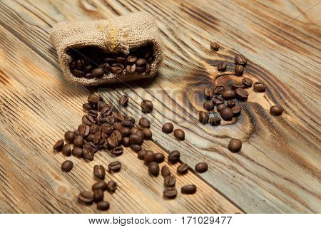 Coffee cup sack scoop of coffee beans on the old wooden floor.