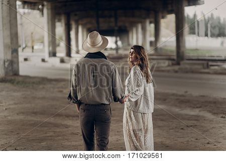 Stylish Hipster Couple Walking And Holding Hands. Man In Hat And Boho Woman In Knitted Sweater Under