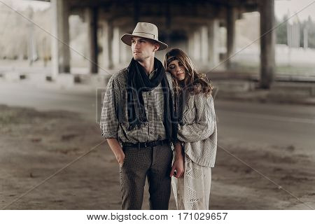 Stylish Hipster Couple Gently Hugging. Boho Woman Touching Arm Of Confident Man In Hat Under Abandon