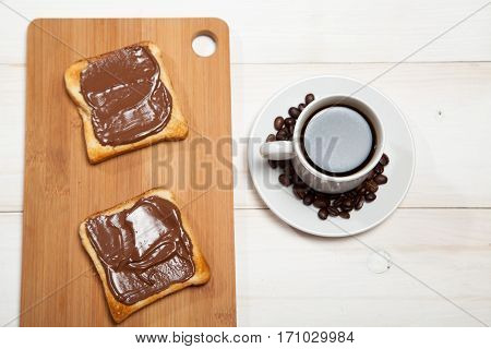 cup of coffee and toast with chocolate on a white wooden table