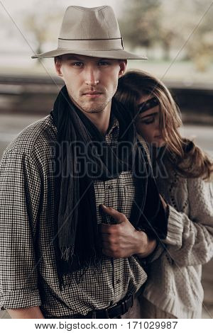 Handsome Cowboy  Man With A White Hat And Black Scarf In A Stylish Shirt Being Hugged By Beautiful I