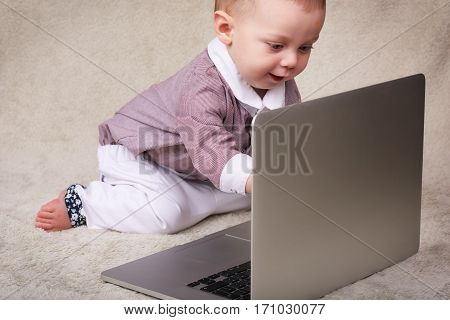 Cute caucasian baby boy using a notebook computer while sitting on a soft blanket getting used to a world of technology.