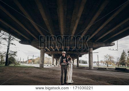 Stylish Hipster Couple Posing Under Abandoned Bridge. Boho Gypsy Woman Gently Hugging Arm Of Confide